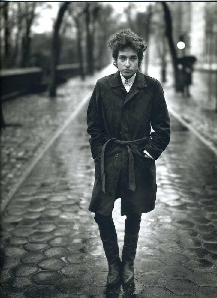 Here Bob Dylan is seen wearing a trendy trench coat, skinny jeans and chlesea boots